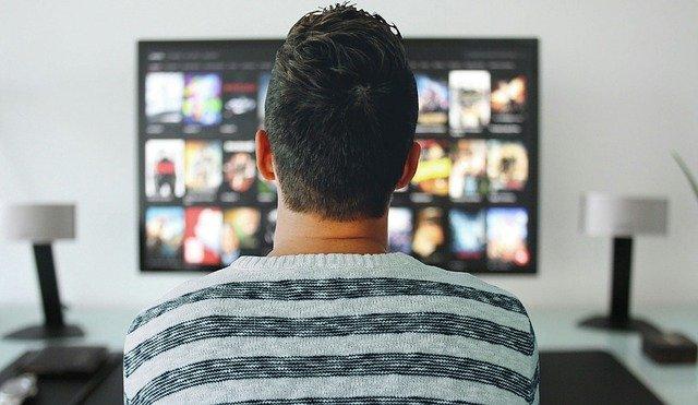 Muž sleduje televizi